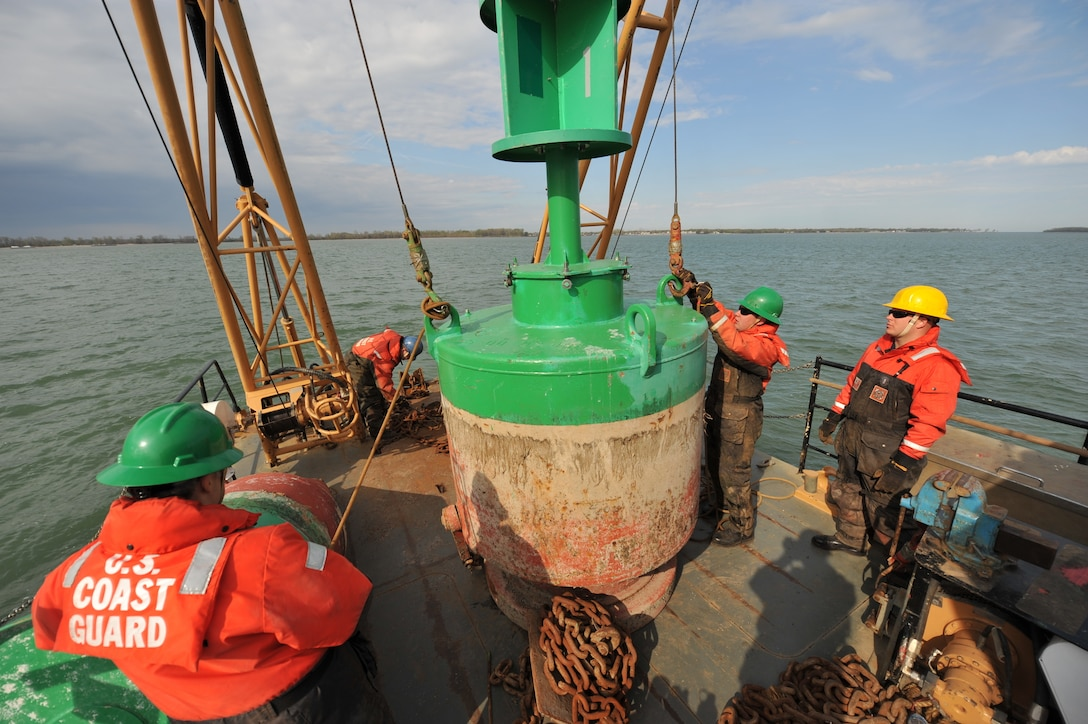 Coast Guardsmen lower a green buoy onto the deck of their boat.