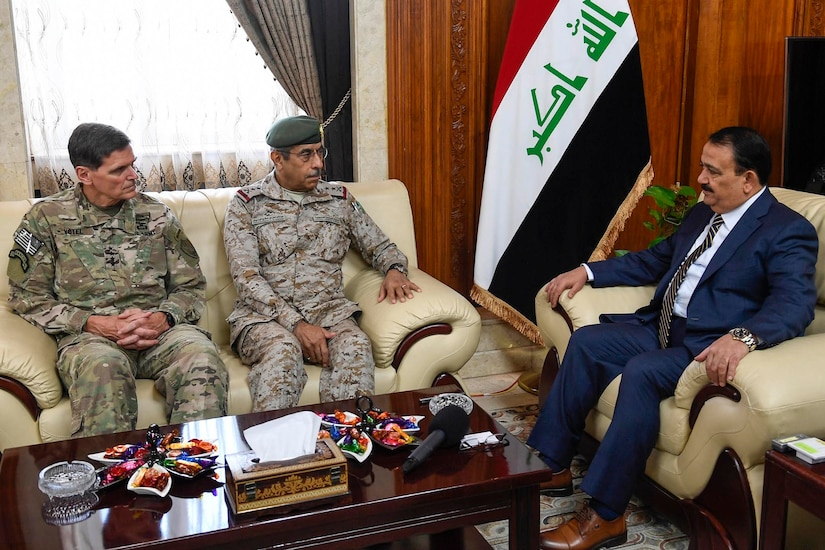 Two generals in uniform sit on a couch facing a man in a civilian suit.