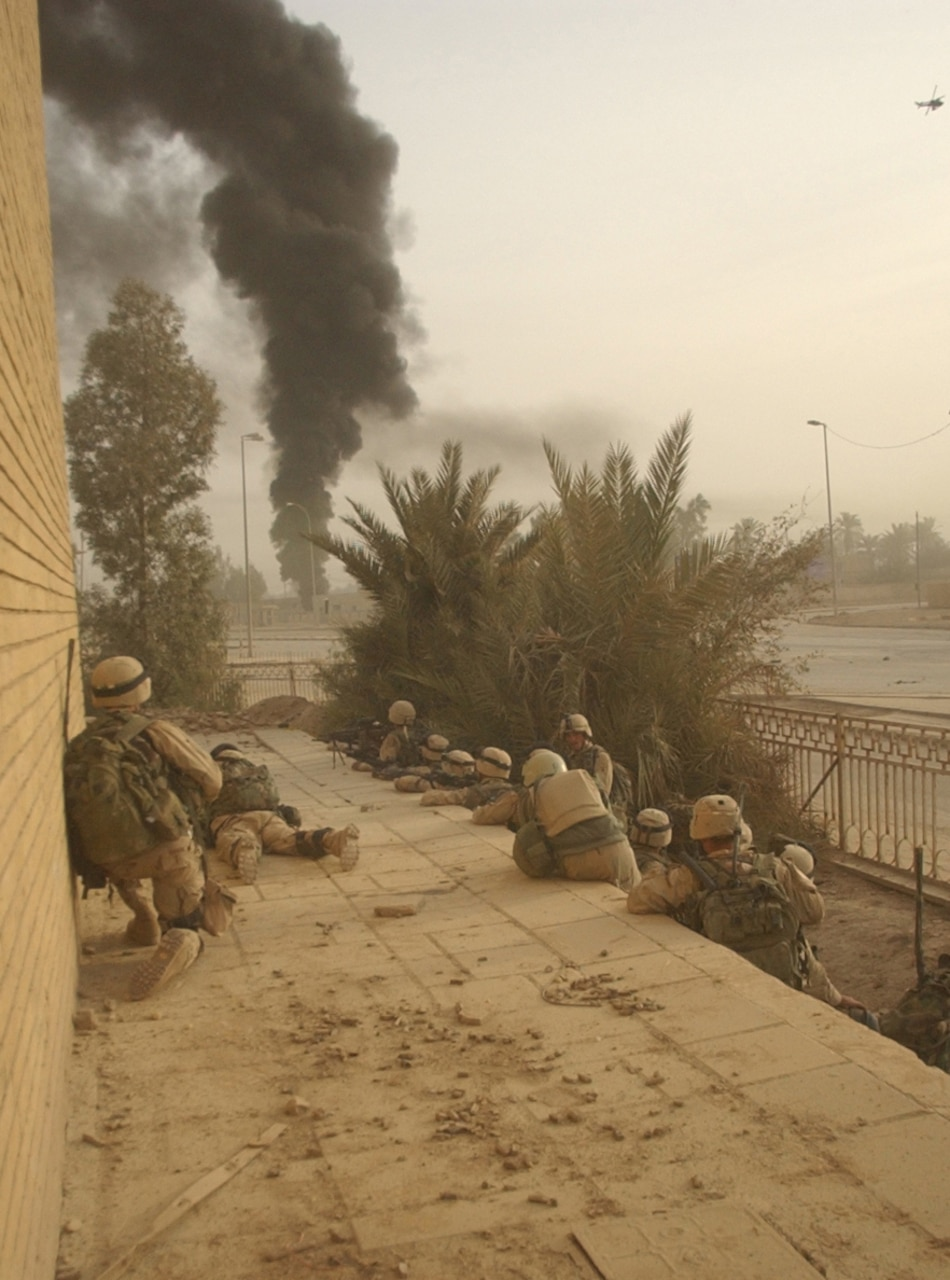 Soldiers huddle near a building with a plume of black smoke in the distance.