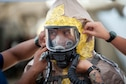 Staff Sgt. James Almero, 154th Medical Group Det. 1 all-hazards-triage-response team member, receives assistance in donning personal protective equipment prior to his rotation into the 'Hot Zone' March 9, 2019, at Kalaeloa, Hawaii.