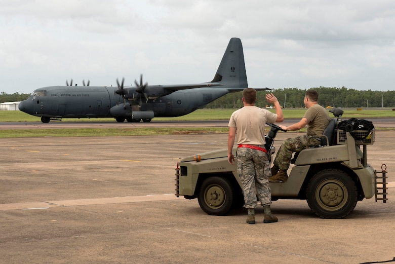 U.S. Airmen assigned to the 5th Maintenance Group wave at a passing Royal Australian Air Force (RAAF) C-130 Hercules during Diamond Shield 2019 (DS-19) at RAAF Base Darwin, Australia, March 26, 2019.