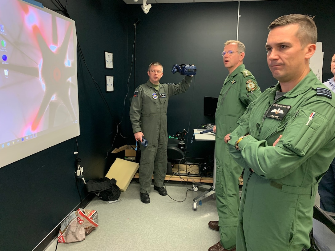 Royal Air Force Flight Lt. Darren French, Pilot Training Next 2.0 instructor pilot and the RAF's senior national representative, highlights virtual-reality headset capabilities to British Army Col. Paddy Logan (center), assistant director for flying training for RAF Headquarters 22 Group, and RAF Squadron Leader Steve Smith (left) at the PTN facility at the Armed Forces Reserve Center in Austin, Texas, March 18, 2019. The RAF have both a student-pilot and an instructor pilot participating in the class as they look to introduce PTN lessons learned into their flying training pipeline. (U.S. Air Force photo/Dan Hawkins)