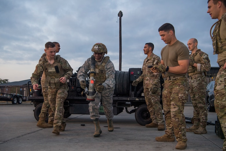 Col. Terrence Adams, 628th Air Base Wing commander, carries a fuel hose during a forward area refueling point team tryout March 26, 2019, at Joint Base Charleston, S.C.