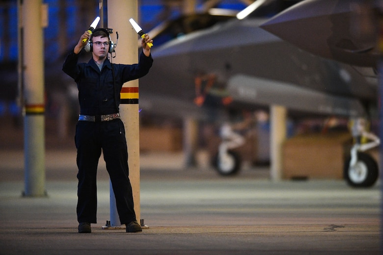 An Airman from the 388th Fighter Wing's 421st Aircraft Maintenance Unit marshals an F-35A Lightning II during night flying operations at Hill Air Force Base, Utah, March 26, 2019. Night flying is required for pilots to sharpen their combat skills and maintainers work around the clock to prepare jets for flight, inspect them after flight, and get them ready for the next flying day. The 388th Fighter Wing is the Air Force's first combat-coded F-35A wing. (U.S. Air Force photo by R. Nial Bradshaw)