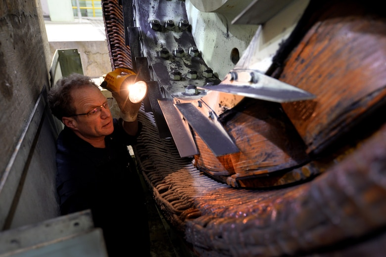 Dave Cormack, 55th Civil Engineer Squadron power support systems mechanic, inspects an alternator for flood damage on Offutt Air Force Base, Nebraska, March 28, 2019. The generators were partially submerged in flood waters following an inordinate amount of snowfall, in the midwest, coupled with several other factors resulted in record-flooding of the adjacent Missouri River.  (U.S. Air Force photo by Josh Plueger)