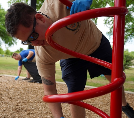 Petty Officer 2nd Class Noe Lopez, assigned to Navy Medicine Education, Training and Logistics Command at Joint Base San Antonio-Fort Sam Houston, disinfects parts of playground during a community relations event held at Martinez Park during a Sailor 360 event.