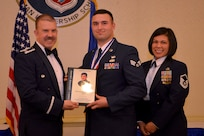 Col. Patrick Winstead, 437th Vice Wing commander, left, and Master Sgt. Calantha Pickel, Airman Leadership School commandant, right, present Senior Airman Cory Germanoff a plaque for earning the John L. Levitow Award during the Airman Leadership School Graduation ceremony March 28, 2019, at the Charleston Club here.