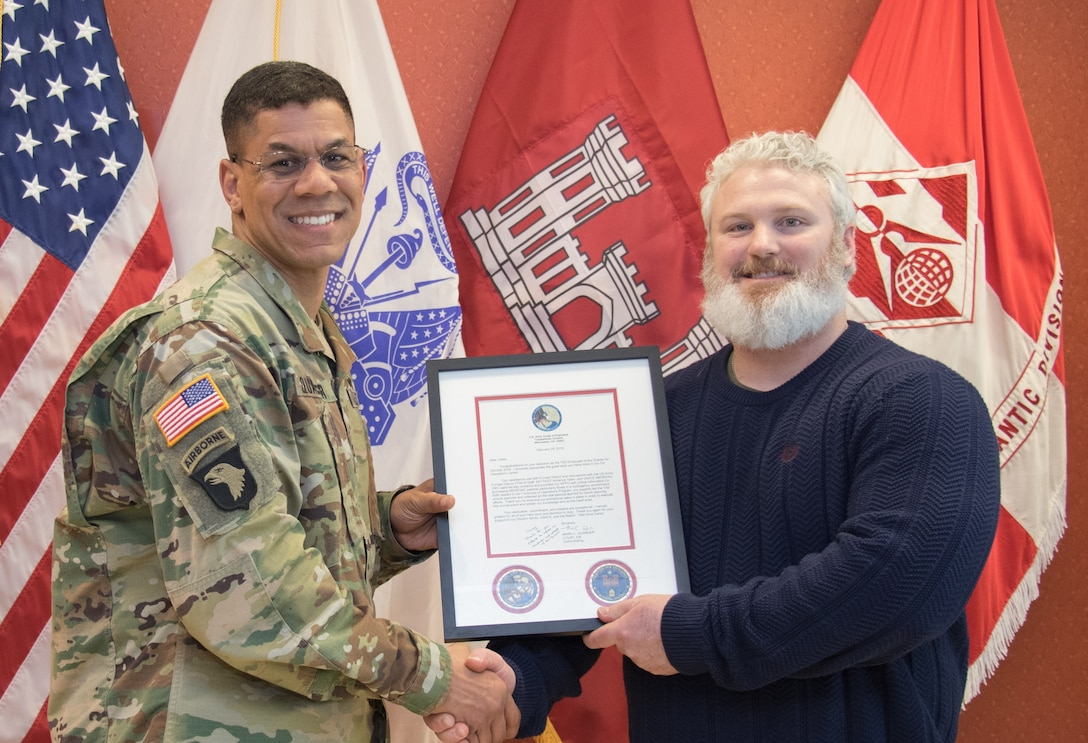 TAD Commander Col. Mark C. Quander, presents the Employee of the Quarter Award for Oct-Dec 2018 to Transatlantic Division Emergency Management Specialist Carey L. Grubbs, during a ceremony held at the TAD headquarters in Winchester, Va. in Feb. 28, 2019. Quander lauded Grubbs for his great work, spearheading several highly visible and planning-intensive initiatives for TAD's Plans and Operations Center.