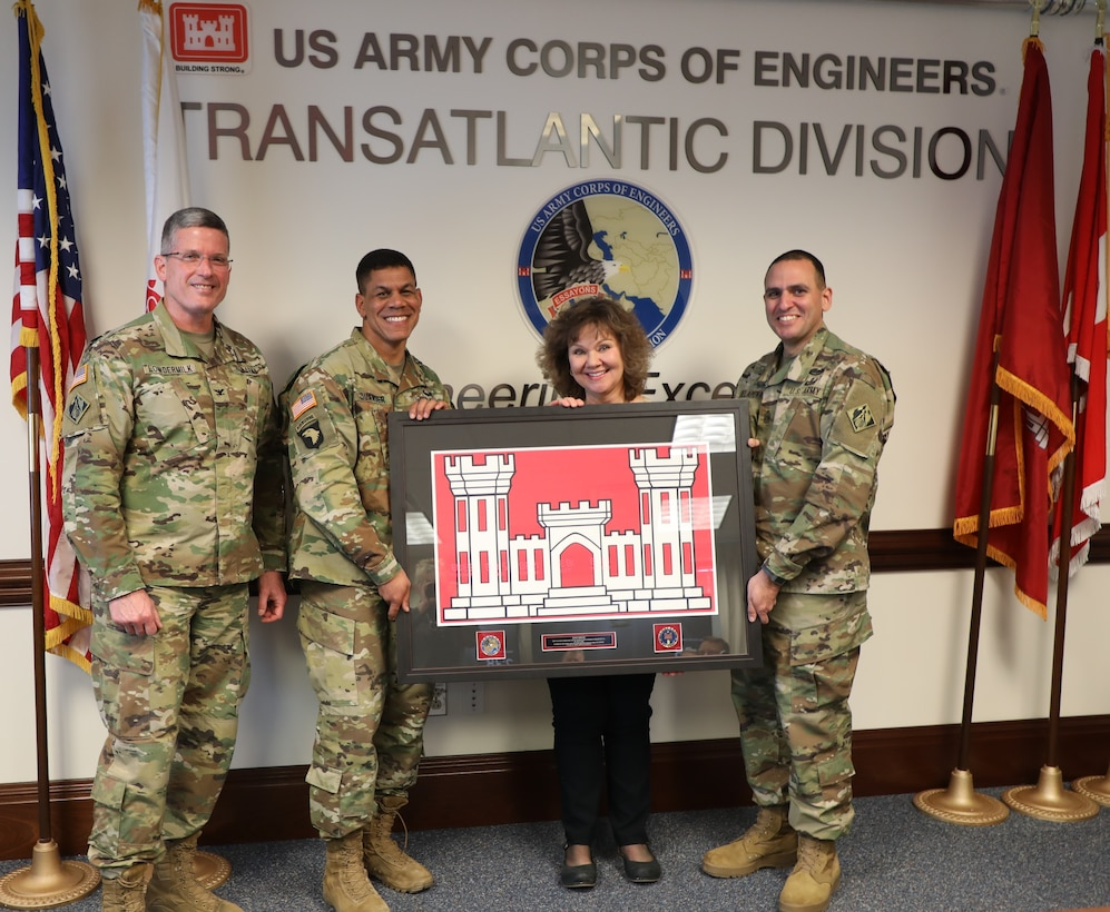 "Members of the Transatlantic Division Command Team present a ""farewell"" gift from TAD employees to Joan Kibler on the occasion of her ""re-retirement."" Kibler was a ""reemployed annuitant"" – a former federal civil servant who came out of retirement to support TAD's Public Affairs office. She retired March 19, 2019, for what she promises is the last time, after 40 years in public service. Pictured (left to right) are Col. Scott Lowdermilk, TAD Commander Col. Mark C. Quander, Kibler, and TAD Command Sergeant Major Randolph Delapena."