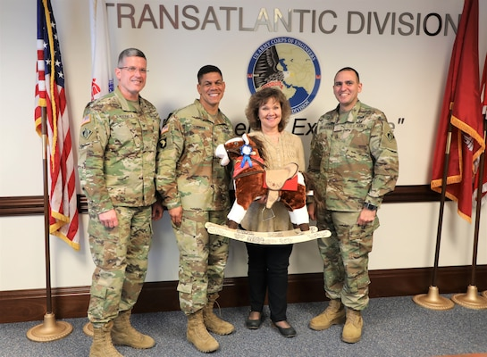 "Members of the Transatlantic Division Command Team present a symbolic ""horse"" from employees to Joan Kibler on the occasion of her ""re-retirement."" Kibler, an avid equine lover, retired March 19, 2019, after 40 years in public service. Pictured (left to right) are Col. Scott Lowdermilk, TAD Commander Col. Mark C. Quander, Kibler, and TAD Command Sergeant Major Randolph Delapena."
