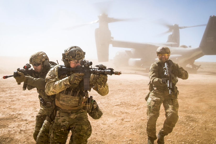 Three service members point rifles in various directions as they move through dust kicked up by an aircraft.