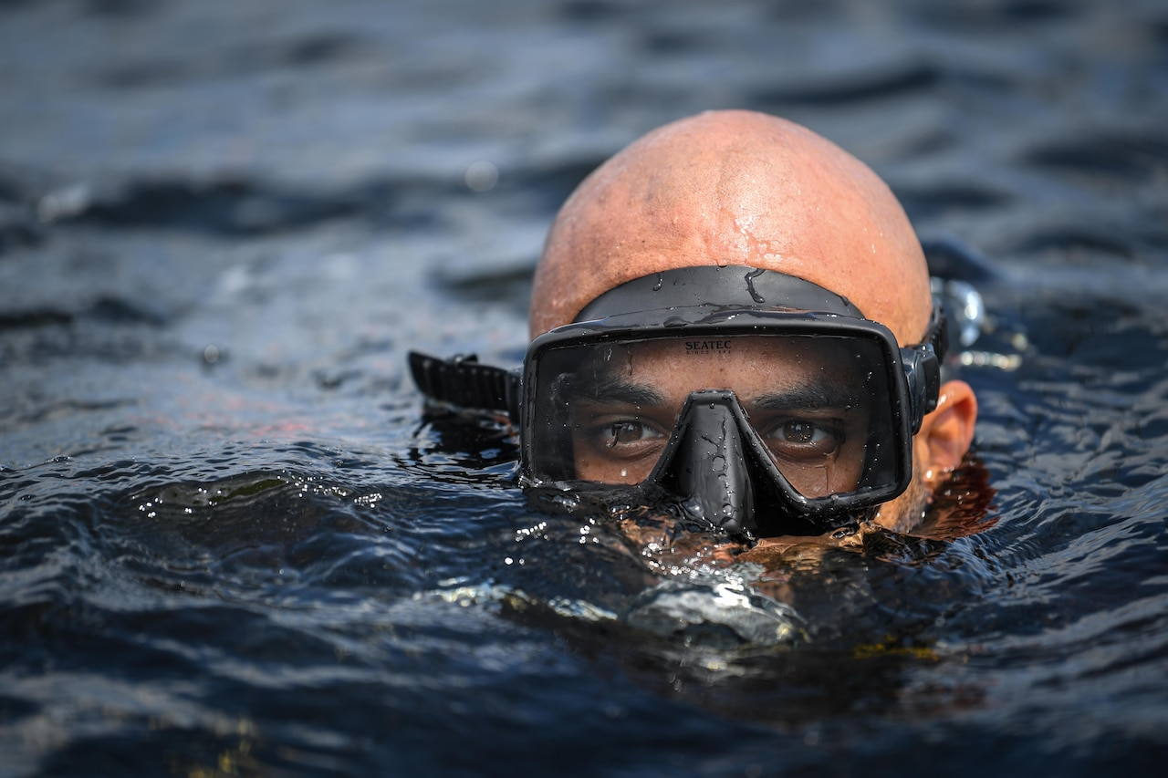 A male diver emerges from water.