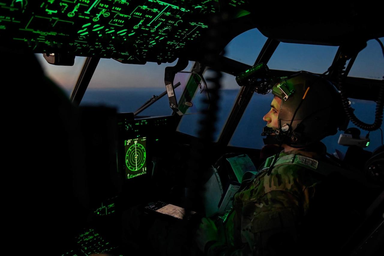 Airmen pilot an aircraft in a darkened cockpit illuminated by green instrument panels.
