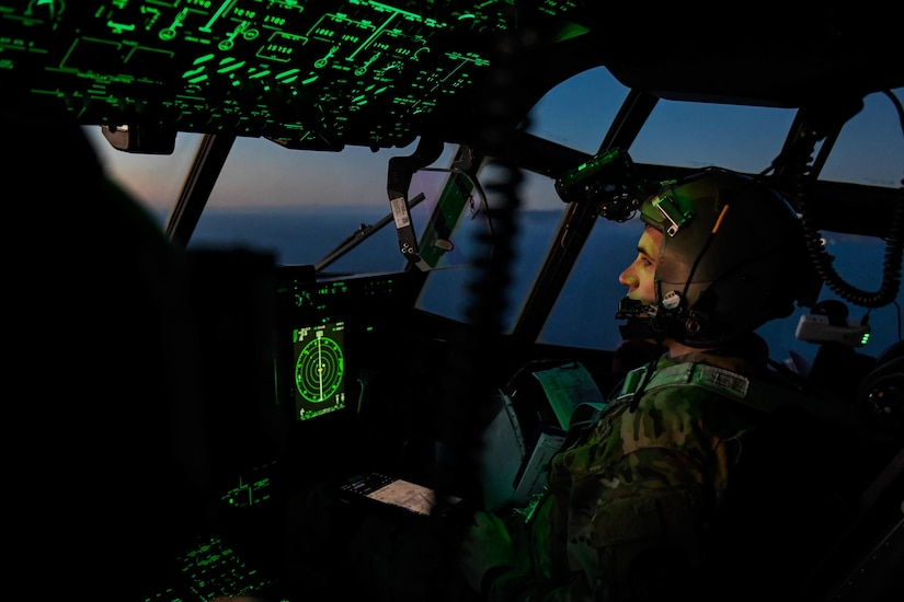 Airmen pilot an aircraft in a darkened cockpit illuminated by green instrument panels.