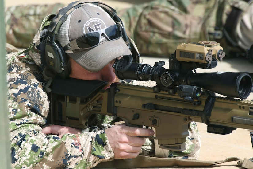 A service member aims a rifle.