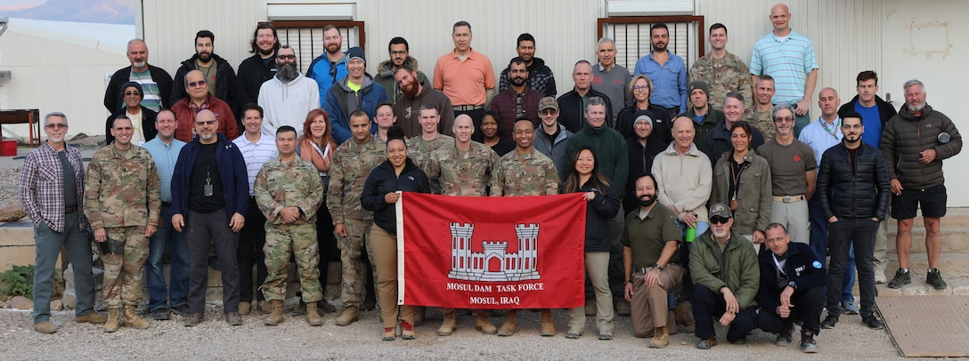 """Members of the U.S. Army Corps of Engineers Transatlantic Division's Task Force Mosul Dam, headquartered in Iraq, pose in front of their building. The team was presented with an award for voting their organization a one of the """"Best Places To Work"""" in the Federal Government."""