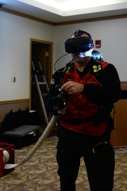 Arpad Lepper, 55th Civil Engineer Squadron fire department training chief, puts out a simulated C-17 aircraft fire March 8, 2019, while using a FLAIM Trainer simulator inside the fire department conference room on Offutt Air Force Base, Nebraska. To help combat the firemen from inhaling harmful toxins during a call, more fire departments are purchasing virtual reality equipment to provide a safer way to train their members. (U.S. Air Force photo by Charles J. Haymond)