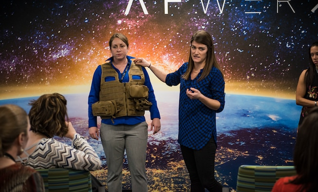 Participants of the Female Flight Equipment Workshop demonstrate issues women face with the current survival vests at AFWERX Vegas, Las Vegas, Jan. 30, 2019. Female Airmen stationed across the globe traveled to attend the workshop to explore areas of opportunity and come up with solutions for their issues. (U.S. Air Force photo by Airman 1st Class Bailee A. Darbasie)
