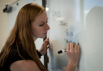 A woman writes on a dry erase board.