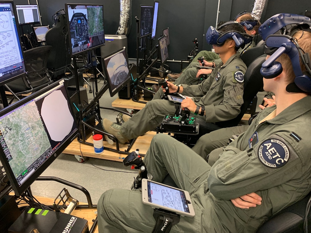 Royal Air Force Flight Officer Syd Janota (fore), Pilot Training Next 2.0 student, observes a fellow student flying a virtual-reality training sortie at the PTN facility at the Armed Forces Reserve Center in Austin, Texas, March 18, 2019. The RAF have both a student-pilot and an instructor pilot participating in the class as they look to introduce PTN lessons learned into their flying training pipeline. (U.S. Air Force photo/Dan Hawkins)