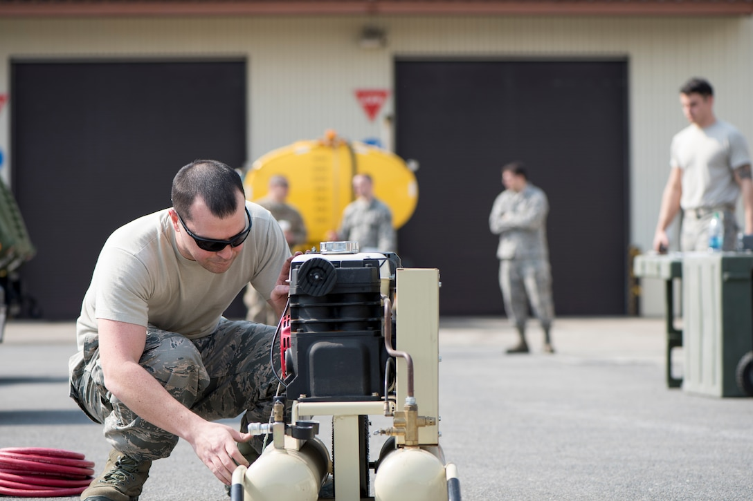 U.S. Air Force Tech. Sgt. Garrett Dicus, the 35th Logistics Readiness Squadron multiple maintenance section chief, inspects an air compressor  during the first LRS Agile Combat Employment exercise at Misawa Air Base, Japan, March 20, 2019. Airmen were only allowed to use a limited amount of mechanical tools such as standard car jacks, fuses, light bulbs, and a generator testing their innovation and personal skillset during an unexpected contingency operations. (U.S. Air Force photo by Airman 1st Class Collette Brooks)