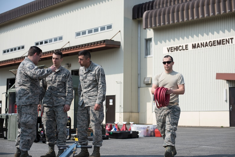 Airmen with the 35th Logistic Readiness Squadron discuss operations and move materials during the first LRS Agile Combat Employment exercise at Misawa Air Base, Japan, March 20, 2019. The exercise challenged the Airmen to determine the tools that were absolutely critical to completing the vehicle operations mission, ensuring that no space is wasted when preparing for contingency relocation operations. (U.S. Air Force photo by Airman 1st Class Collette Brooks)