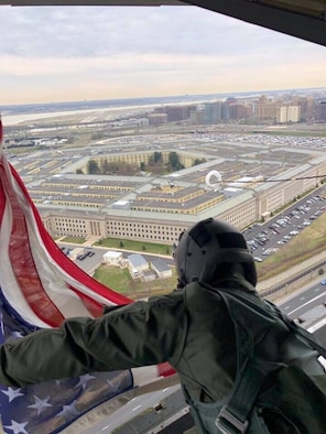 While gripping the corners of an 5x9-foot American Flag, combat rescue loadmaster, Air Force Master Sgt. Dean Scalise, and his 39th Rescue Squadron crew, piloted an HC-130N combat-search-and-rescue aircraft sailed over Arlington National Cemetery to honor Air Force Colonel Rick A. Kibbey, a fellow rescue aviator, was brought home from Vietnam after being missing in action for more than 50 years after a farmer located his dog tags in Vietnam and turned them in to authorities allowing his family to lay him to rest on March 29, 2019, Vietnam War Veterans Day. (U.S. Air Force photo)