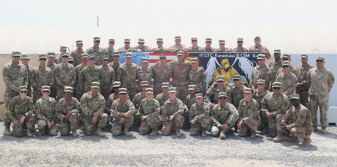 Soldiers of the 420th Transportation Battalion, a U.S. Army movement control battalion, gather at their memorial T-Wall at Camp Arifjan, Kuwait, April 27, 2019.