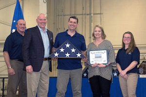 Airman receiving retirement flag and certficate.