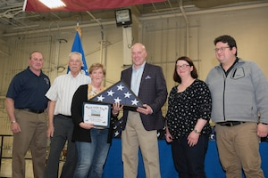 Airman receiving retirement flag and certificate.