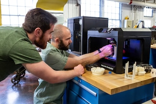 Brendon Wilkins and Matthew Perkinson from Norfolk Naval Shipyard's Technology and Innovation (T&I) Lab, work on a 3-D printer.