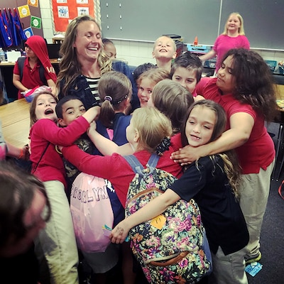 Valerie Stearns gets an end-of-the-year hug from her third-grade class at Fostoria Elementary School in Fostoria, Ohio. Stearns, a first lieutenant in the Ohio Army National Guard, has found ways to develop her competitive spirit in developing young minds and in uniform.