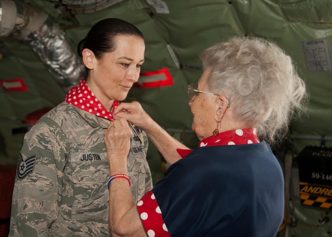 "Mae Krier, an original ""Rosie the Riveter"" who helped build B-17s and B-52s during WWII, ties a bandana on Tech Sgt. Kat Justen, 459th Air Refueling Wing, non-commissioned officer in charge of Public Affairs, while on a tour at the 459th Air Refueling Wing at Joint Base Andrews, Md., April 30, 2019. Krier became a fan of Tech Sgt. Justen after seeing her popular art work hanging in the Air Force wing at the Pentagon. (U.S. Air Force photo by Staff Sgt. Cierra Presentado)"