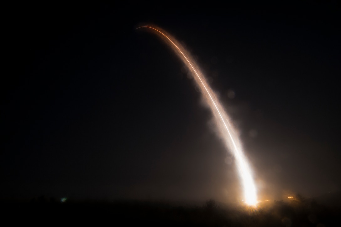 The fiery trail of a missile lights up a dark sky.