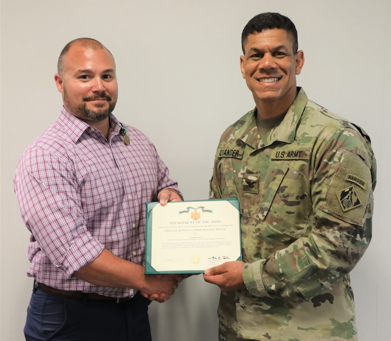 TAD Commander Col. Mark C. Quander, presents the Civilian Service Commendation Medal to Bahrain Program Manager Peter DeMattei, during a ceremony held at the TAD headquarters in Winchester, Va., on April 25, 2019. Quander lauded DeMattei for his work performance leading the Bahrain Project Deliver Team.