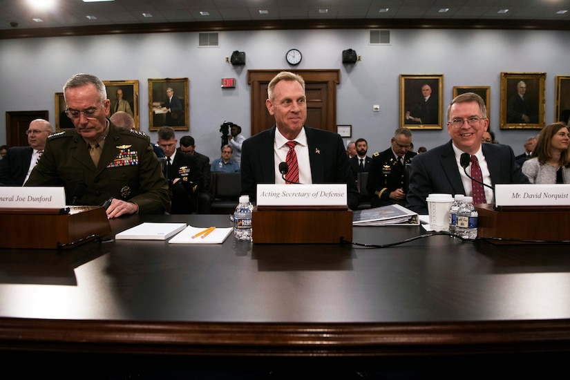 Three defense leaders sit behind a long desk.