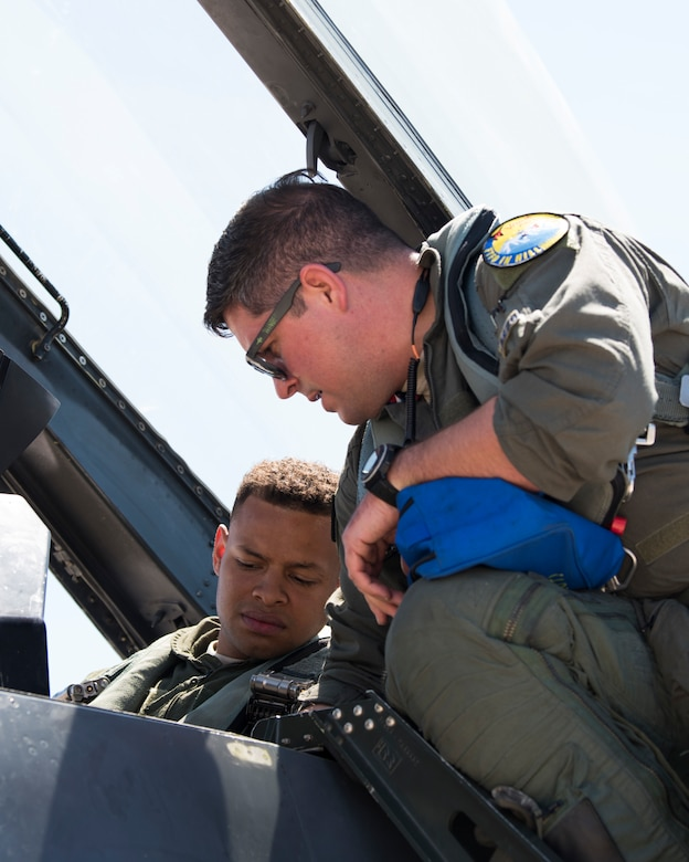 Maj. Jon Farragher, 311th Fighter Squadron assistant director of operations, helps Airman 1st Class Mequail Fridge, 311th Aircraft Maintenance Unit crew chief, buckle into the ejection seat of an F-16 Viper, April 25, 2019, on Hill Air Force Base, Utah. The 311th FS had a goal of eight familiarization flights per day for operations and maintenance personnel during exercise Venom 19-01. (U.S. Air Force photo by Staff Sgt. BreeAnn Sachs)