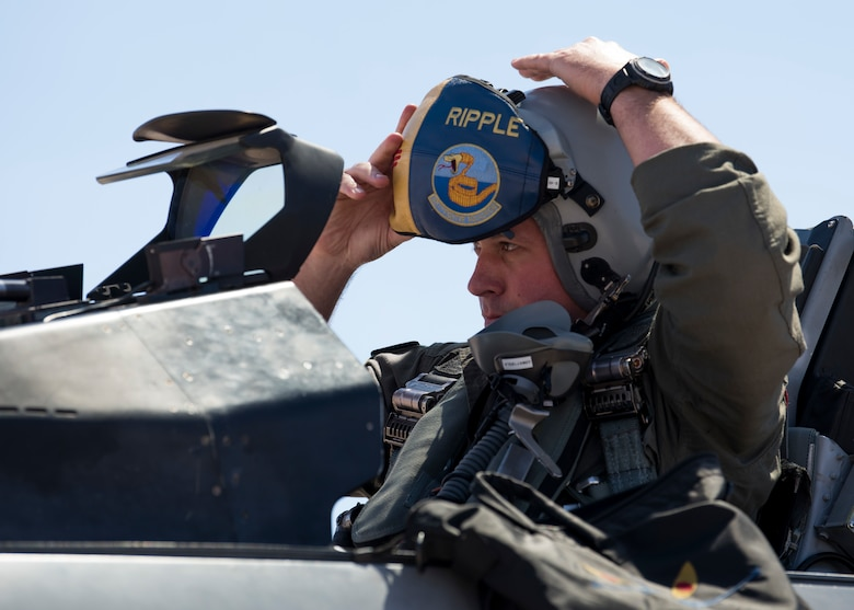 Maj. Jon Farragher, 311th Fighter Squadron assistant director of operations, dons his helmet before flying a familiarization flight for Airman 1st Class Mequail Fridge, April 25, 2019, on Hill Air Force Base, Utah. The goal of a FAM flight is to educate ground personnel about their impact on the mission. (U.S. Air Force photo by Staff Sgt. BreeAnn Sachs)