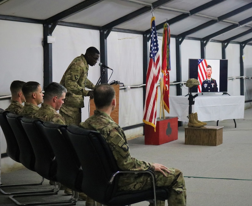 Spc. Chad Williams, 101st Airborne Division, speaks as a close friend of Spc. Ryan Riley during a memorial service at Qayyarah West Airfield, Iraq, March 25, 2019.