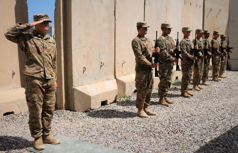 Sgt. Jeffery Love, 101st Airborne Division, leads the  firing of three rifle volleys in respect for Spc. Ryan Riley during a memorial service at Qayyarah West Airfield, Iraq, March 25, 2019.