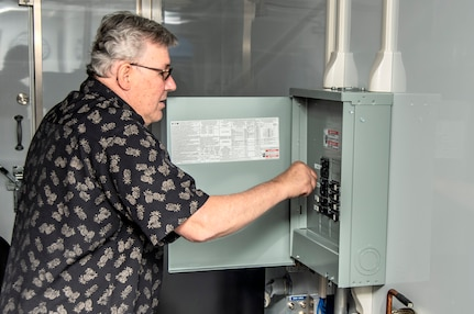 Rick Heinly, Logistics Management Specialist at Naval Surface Warfare Center, Port Hueneme Division, supplies power to the newly established Mobile Command center at Port Hueneme. The center is part of the command's efforts to provide Navy ships with mobile repair capability.