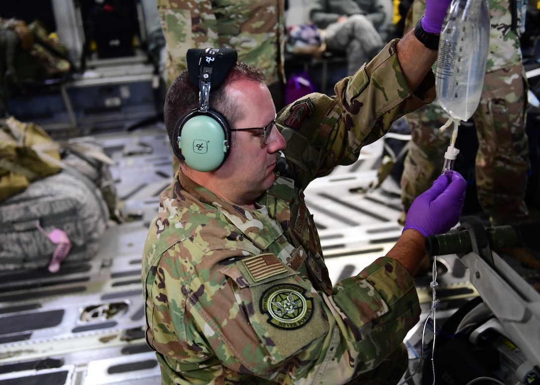 Master Sgt. Joseph Vergona, 911th Aeromedical Evacuation Squadron medical technician, sets up a saline bag near Honolulu, Hawaii April 26, 2019. As a part of the 911th AES Vergona participated in ground training as well as in air training.(U.S. Air Force Photo by Senior Airman Grace Thomson)