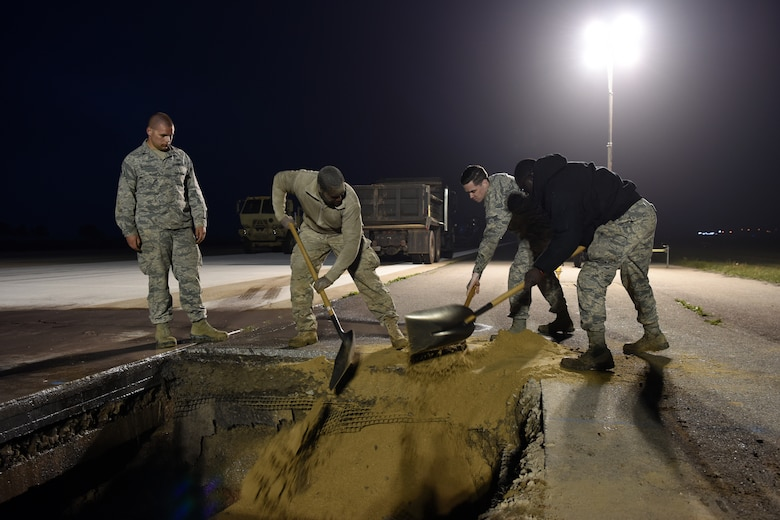 U.S. Air Force 8th Civil Engineer Squadron members shovel dirt into a hole on the flight line at Kunsan Air Base, Republic of Korea, May 1, 2019. 8th CES and 8th Logistics Readiness Squadron worked through the night to get the flight line operational again after it was closed unexpectedly due to a rupture. (U.S. Air Force photo by Staff Sgt. Joshua Edwards