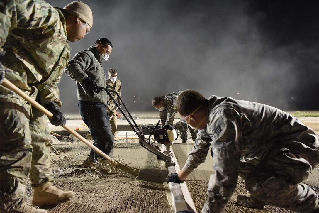 U.S. Air Force 8th Civil Engineer Squadron members smooth concrete on the flight line at Kunsan Air Base, Republic of Korea, May 2, 2019. The 8th CES applied rapid airfield damage repair methods to fix a rupture that caused damage to the flight line. (U.S. Air Force photo by Staff Sgt. Joshua Edwards)
