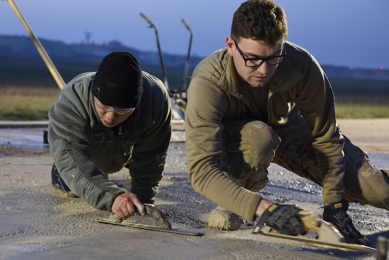 (Left) U.S. Air Force Tech Sgt. Jonathan Shinsato and Staff Sgt. Jeffrey Deptula, 8th Civil Engineer Squadron pavement and construction equipment journeymen, smooth wet concrete on the flight line at Kunsan Air Base, Republic of Korea, May 2, 2019. The 8th CES conducted a rapid response to a rupture that opened on the runway, and repaired the flight line within 24 hours. (U.S. Air Force photo by Staff Sgt. Joshua Edwards)