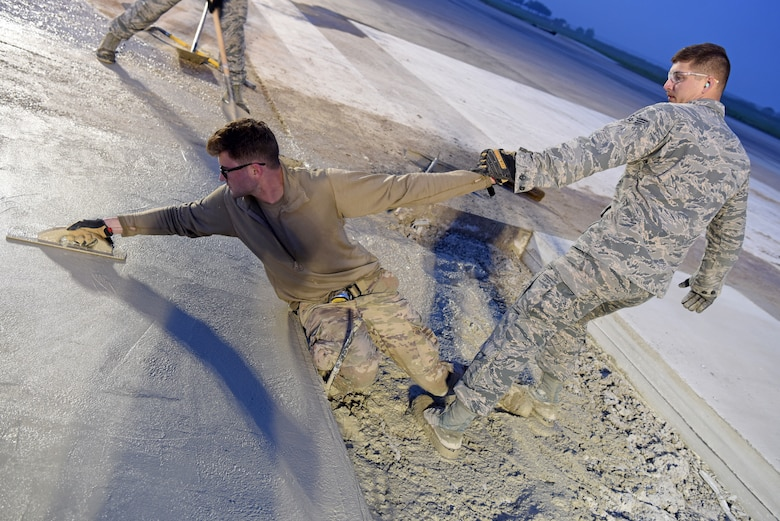 (Right) U.S. Air Force Senior Airman Steven Uhlbeck, 8th Civil Engineer Squadron pavement and construction equipment journeyman, assists Staff Sgt. Jeffrey Deptula, 8th CES, with smoothing wet concrete on the flight line at Kunsan Air Base, Republic of Korea, May 2, 2019. The 8th CES applied rapid airfield damage repair methods to fix a rupture that caused damage to the flight line. (U.S. Air Force photo by Staff Sgt. Joshua Edwards)