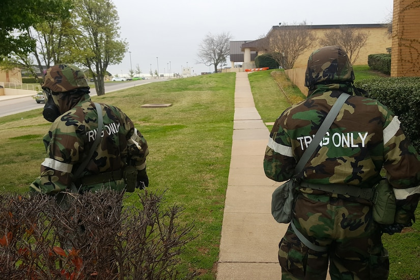 Two soldiers walk along a sidewalk.