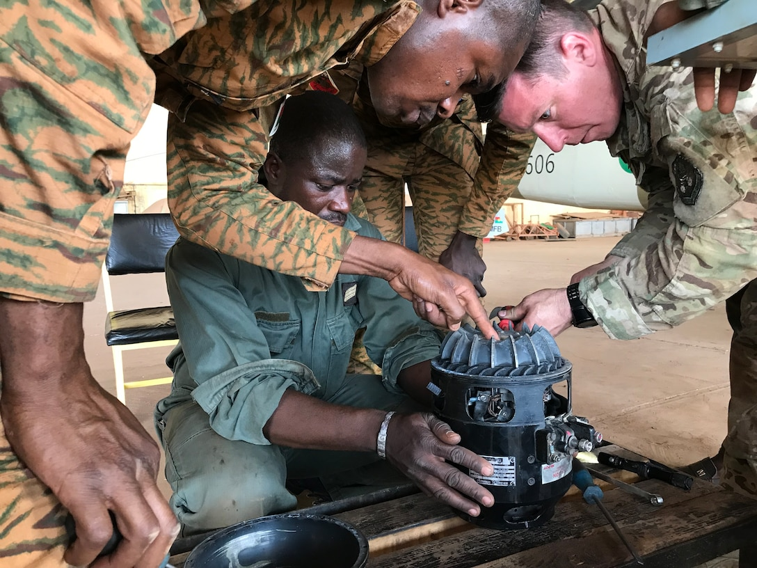 Master Sgt. Russ Asbel, right, 582nd Helicopter Group aircraft maintainer, inspects a main helicopter generator with mechanics from the Burkina Faso Air Force at Airbase 511 in Burkina Faso, Africa, April 10, 2019. Asbel augmented the 818th Mobility Support Advisory Squadron during their building partner capacity engagement to Burkina Faso, Africa, April 5-20. (U.S. Air Force photo by Master Sgt. Sarah Colwell)