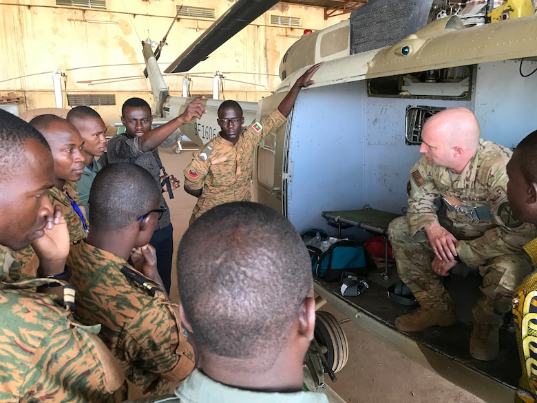 Master Sgt. Todd Chandler, right, 40th Helicopter Squadron flight engineer, leads a small group discussion focusing on aircrew in-flight responsibilities and post flight inspections with flight engineers and mechanics from the Burkina Faso Air Force at Airbase 511 in Burkina Faso, Africa, April 11, 2019.  Chandler augmented the 818th Mobility Support Advisory Squadron during their building partner capacity engagement to Burkina Faso, Africa, April 5-20. (U.S. Air Force photo by Master Sgt. Sarah Colwell)