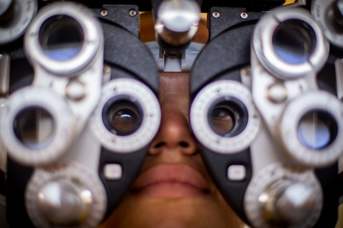 A patient looks through an illuminated phoropter refracting instrument at Yauco, Puerto Rico, April 28, 2019, during Innovative Readiness Training Puerto Rico. IRT Puerto Rico is also called Ola de Esperanza Sanadora, which translates to Healing Wave of Hope. This IRT is part of a civil and joint military program to improve military readiness while simultaneously providing quality services to underserved communities throughout the United States. (U.S. Marine Corps photo by Sgt. Andy O. Martinez)